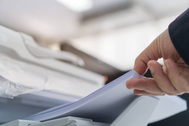 imprimante d'affaires/documents d'impression dans le concept de bureau: homme d'affaires presse le papier blanc dans le chargeur de cartouche imprimé au laser, machine de scanner pour le document de copie à rapporter dans le fond occupé de bureaux - presse photos et images de collection