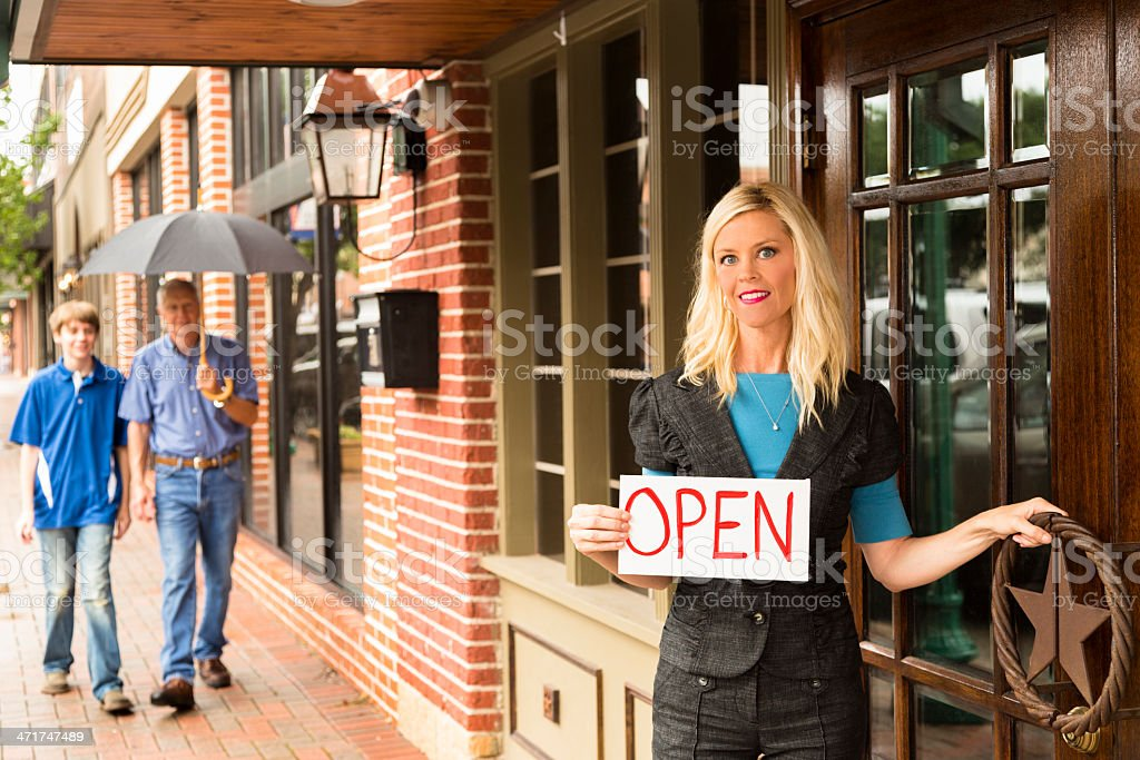 Business: Professional female entrepreneur with OPEN sign at store front. royalty-free stock photo