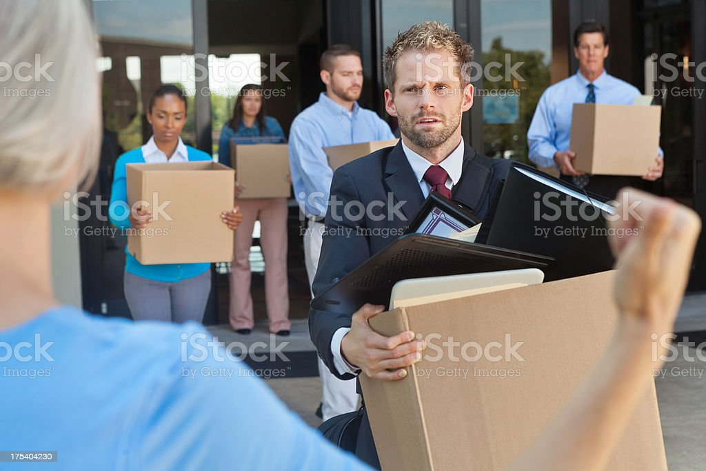 Business professionals being fired or laid off leaving office stock photo