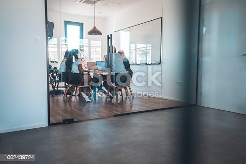 Web designers discussing at conference table in board room. Business professionals are in meeting at creative office. They are seen through glass door at workplace.