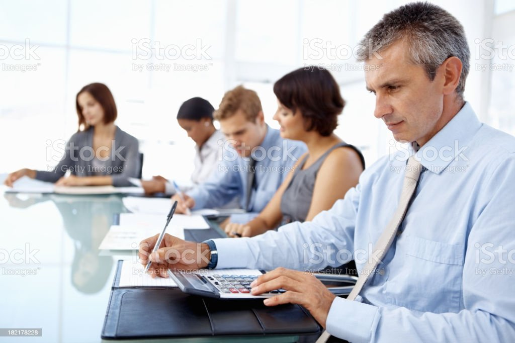 Business professionals reviewing notes and using calculators royalty-free stock photo