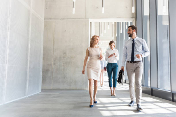 Business professionals talking while walking in office corridor stock photo