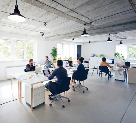 Male and female professionals working in new office. Business executives are discussing while sitting by desk at creative workplace. They are in casuals.