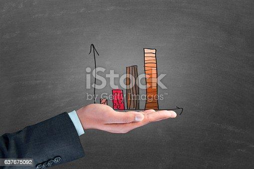Businessman holding bar graph business report over blackboard
