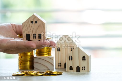 business real estate investment or loan concept : miniature wooden house on hands with money coins. Ideas to reverse mortgage transform to cash borrower, decide buy new residential in life