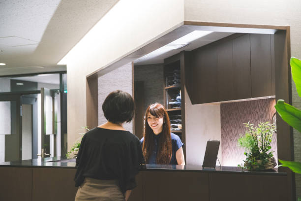 Business reception - woman standing greeting guests in lobby stock photo