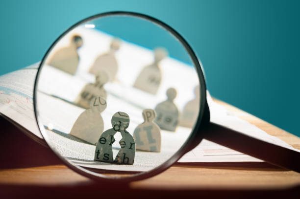 Business recruitment or hiring photo concept. Business recruitment or hiring photo concept. Looking for talent. Icons of candidates are standing on open newspaper under magnifier. scrutiny stock pictures, royalty-free photos & images