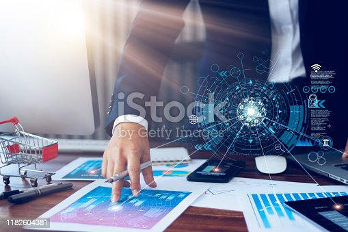 865596974istockphoto Business report, analysis and planning, Businessman hand pointing at business document and a tablet, mobile phone displaying financial data with icon network connection background. 1182604381