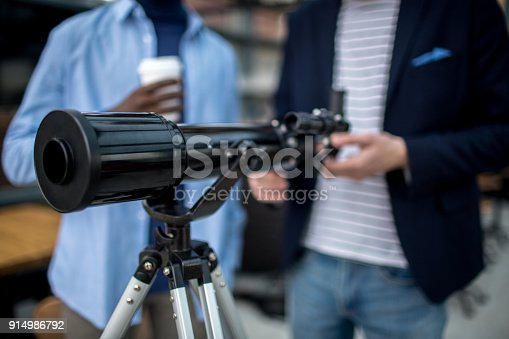 Professional telescope on tripod and two young men going to use it