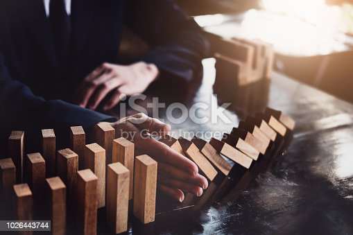 istock Business risk control concept, Businessman protect wooden block fall to planning and strategy in risk to business Alternative and prevent. Investment Insurance Business. 1026443744