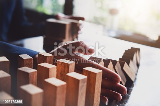 istock Business risk control concept, Businessman protect wooden block fall to planning and strategy in risk to business Alternative and prevent. Investment Insurance Business. 1097175366