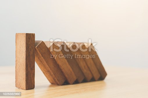 istock Business risk management concepts. Wooden block stop falling of other pieces of domino effect. 1025332992