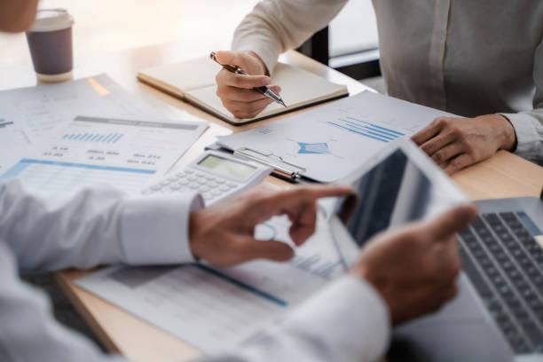 konsultan penjualan bisnis berdiskusi dalam dokumen data di kantor modern. - cpa vs tax advisor potret stok, foto, & gambar bebas royalti