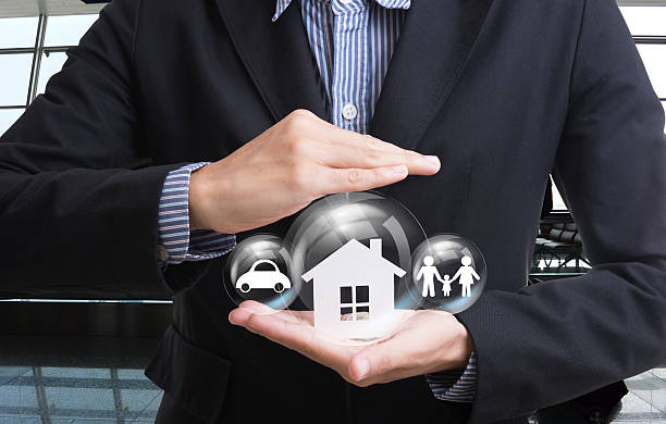 business salesman hand holding home, car, family stock photo