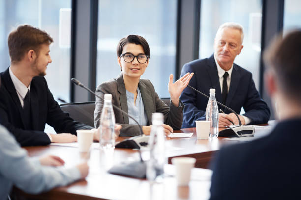 Business Seminar Portrait of young businesswoman speaking to microphone during group discussion in conference room, copy space debate stock pictures, royalty-free photos & images
