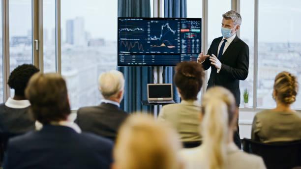 Business seminar. Speaker in face mask analyzing post pandemic stock market stock photo