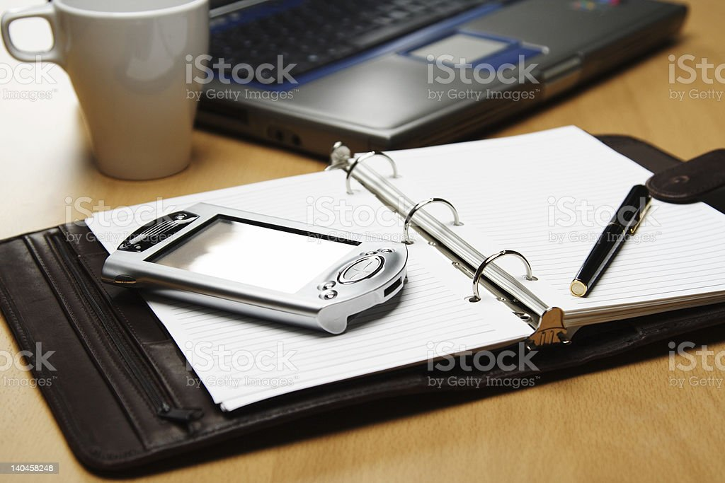 Business setting of day planner, phone, pen, mug and laptop stock photo
