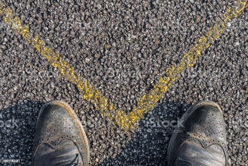Business Shoes and yellow mark on asphalt stock photo