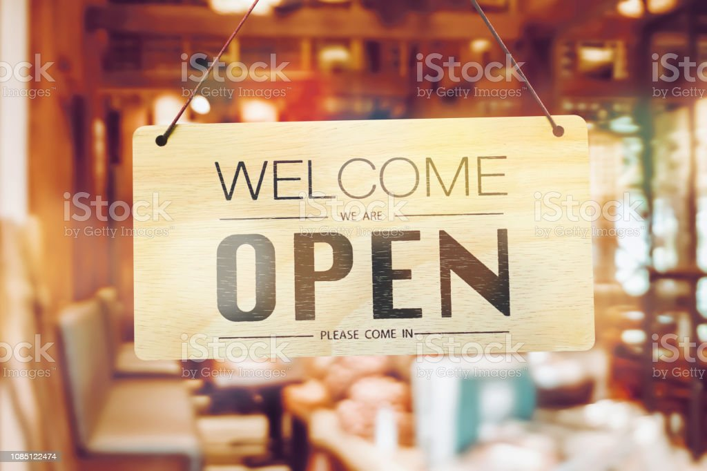 A business sign that says 'Open' on cafe or restaurant hang on door...