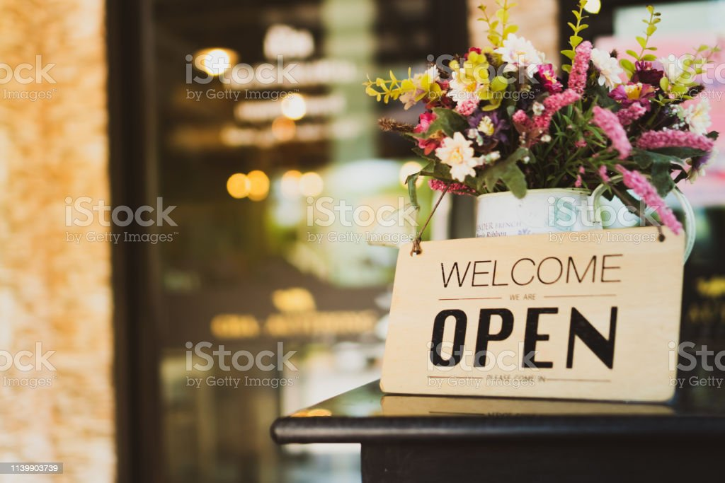 A business sign that says open on cafe or restaurant hang on door at...