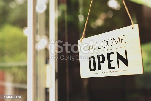 "istock A business sign that says ""u2018Open""u2019 on cafe or restaurant hang on door at entrance. Vintage color tone style. 1298039173"