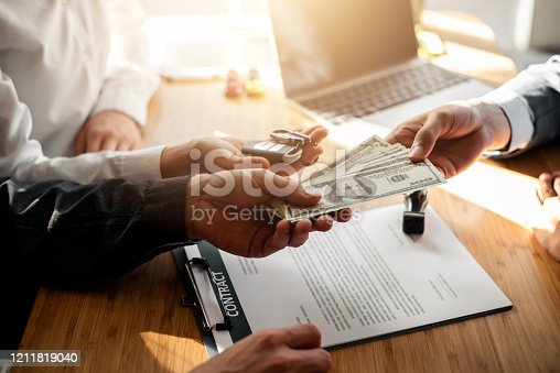 939005154 istock photo Business signing a contract buy - sell car. Young couple is signing buy or sales car contract and gets the key for the new car. 1211819040