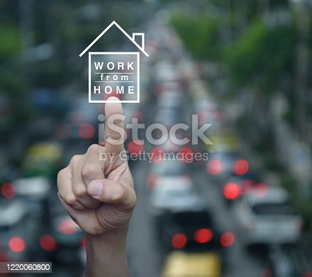 Hand pressing work from home flat icon over blur of rush hour with cars and road in city, Business social distancing concept