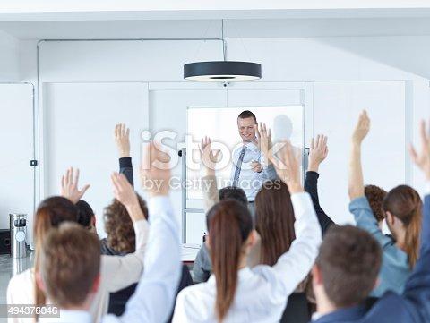 Businessman giving presentation. Raising hands in seminar.