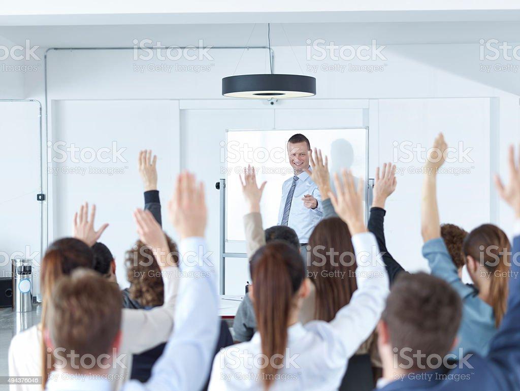 Business Spectators Or Students Raising Hands In Seminar stock photo