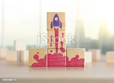 istock Business start up, start, new project or new idea concept. Wooden blocks with launching rocket graphic arranged in pyramid shape. 1094465770