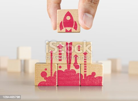 istock Business start up, start, new project or new idea concept. Wooden blocks with launching rocket graphic arranged in pyramid shape and a man is holding the top one. 1094465798