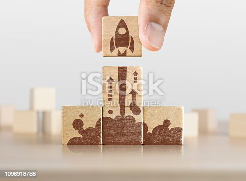 istock Business start up, start, new project or new idea concept. Wooden blocks with launching rocket graphic arranged in pyramid shape and a man is holding the top one. 1096918788