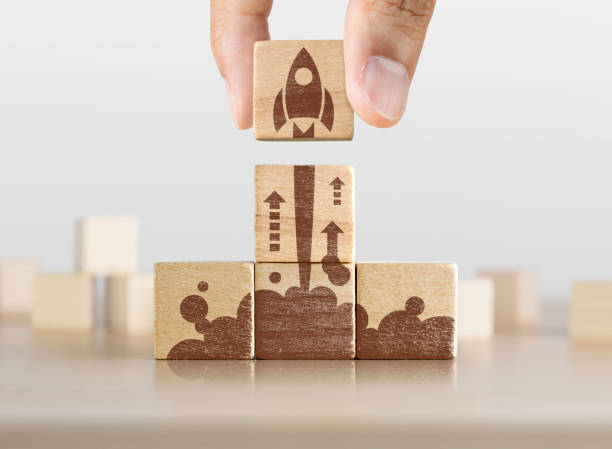 business start up, start, new project or new idea concept. wooden blocks with launching rocket graphic arranged in pyramid shape and a man is holding the top one. - nuova impresa foto e immagini stock