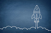 Business startup concept with space shuttle drawing on blue chalkboard