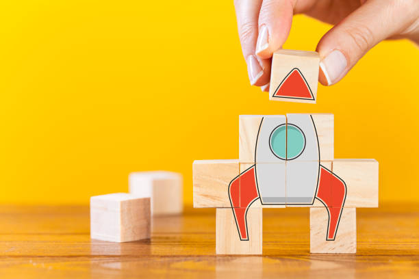 Business startup Hand arranging wooden cubes in a structure rocket shape. Conceptual of business startup and strategy. publicity event stock pictures, royalty-free photos & images