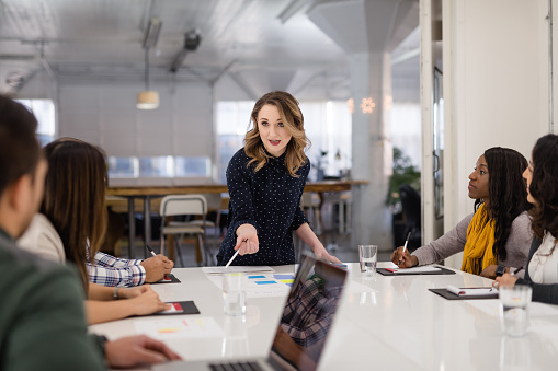 A multiethnic business team gathers around a conference table to finalize documents for the launch of their new startup. A Caucasian female is standing at the head of the table and guiding the discussion.