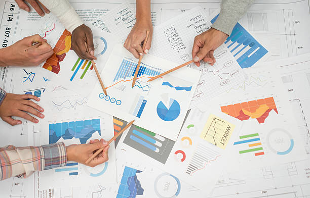 Business statistic documents Group of workers at a business meeting looking at statistics documents in a creative office market research stock pictures, royalty-free photos & images