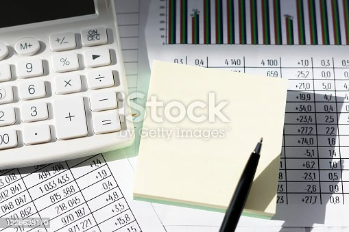 490632340 istock photo Business still-life of a black pen, yellow stickers, graph, white calculator in the sun. 1226638170