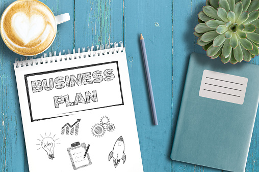 business strategy concept, top view of business plan on notepad on rustic wooden table