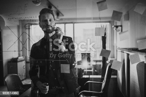Photo of businessman writing on the glass wall in the office