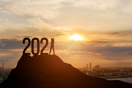 Business success concept in new year 2021. A businessman with a raised hand stands with numbers on the top of the mountain.