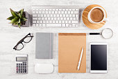 Business table top with office supplies on white wooden table background
