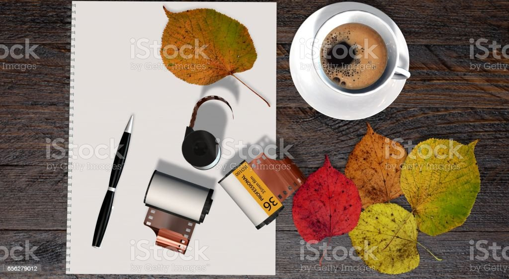 Business table with 35mm camera photo film canisters, coffe and white notepad stock photo