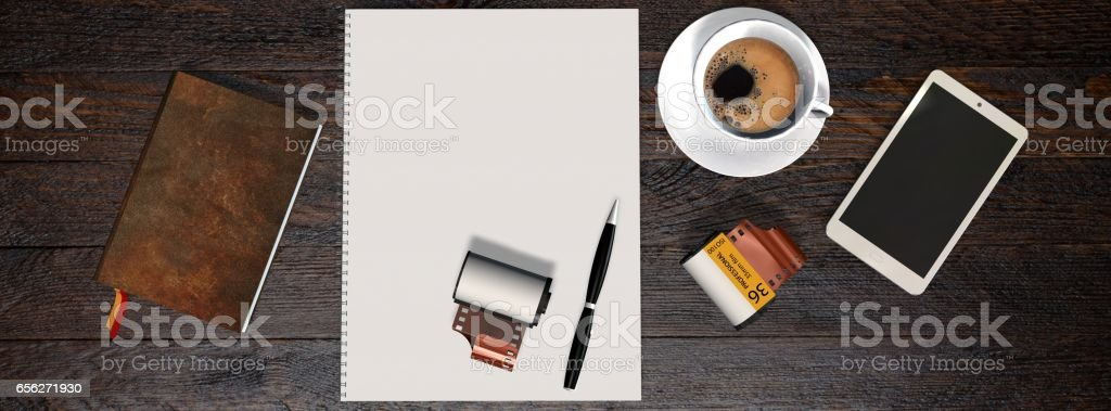 Business table with 35mm camera photo film canisters, coffe, smartphone, notebook and white notepad stock photo