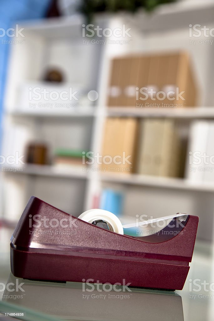 Business:  Tape dispenser sitting on office desk.  Bookcases background royalty-free stock photo
