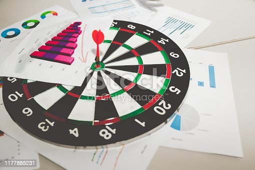 Business target goal concept, Circular target marked with numbers and red dart against document of graph stat background