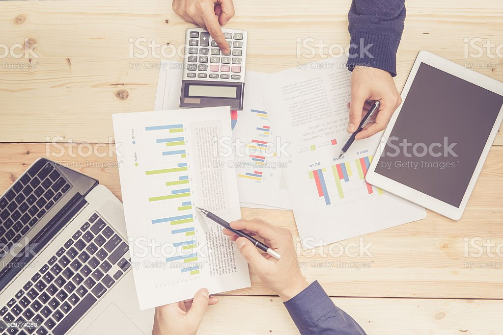 Business team analyzing charts and graphs stock photo