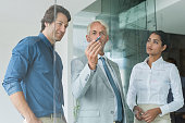 Business team planning a new strategy standing in front of glass wall drawing graph. Leaderhip thinking while drawing graph on glass in office. Business team discussing about growth with help of statistics during a meeting.