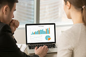Businessman and businesswoman analyzing project statistics data on laptop screen, partners discussing infographic information about company growth, annual report analysis, close up rear view
