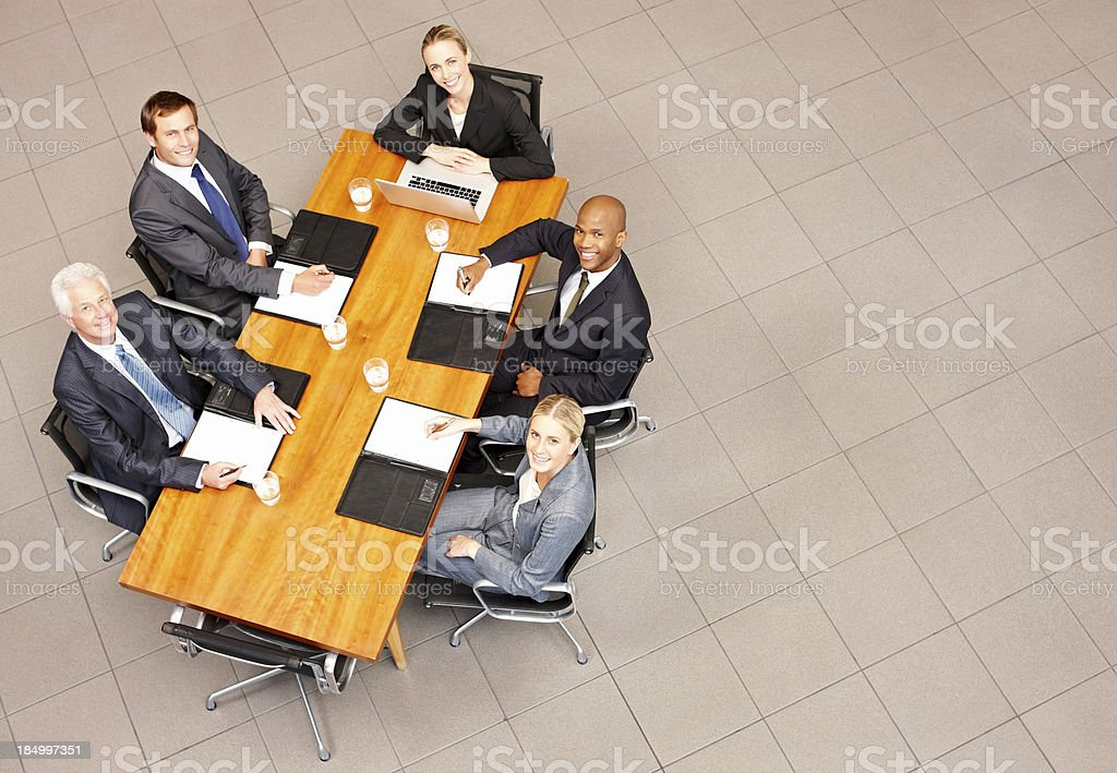 Overhead view of business people looking up from a conference table....